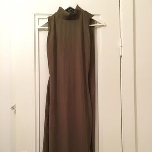Snygg midiklänning, militärgrön. Bar rygg med ett band som kan knytas på många olika sätt, slits på sidan. Oanvänd