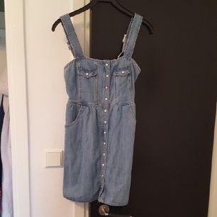 Fin jeansklänning från Monki. Färgen är något blåare i verkligheten. Axelbanden är justerbara & den går (på min som är 172 cm lång) strax under mitten på låret. Priset är inklusive frakt🎈