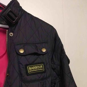 Barbour jacka storlek 36, kan även passa en 34. Mörkblå/limaktig färg med rosa innefoder. Använd en säsong.