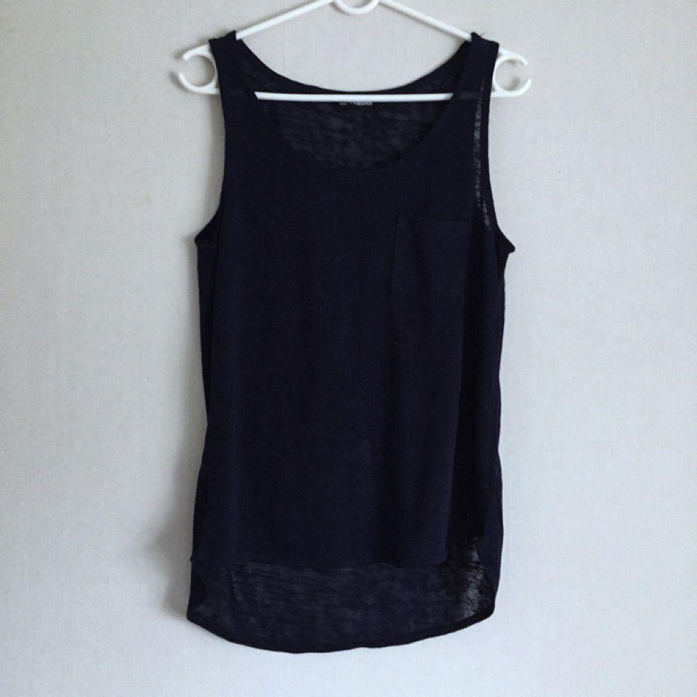 Mörkblått linne från Kappahl gjort i ett tunnare tyg som ter sig en aning genomskinligt. Lite längre i bak. Helt oanvänt. . Toppar.