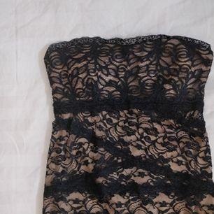 Kort spetsklänning från Bebe i strl S, använd en gång och är i fint skick. Har tjockare tyg under spetsen och tunt trasparent tyg bredvid dragkedjan bak på ryggen. Halterneck-band medföljes. Kan skicka fler bilder vid intresse!