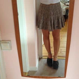 Vintage-kjol i brun-svart-vittmönster. Knappen där bak är borta men dragkedjan fungerar. Lite