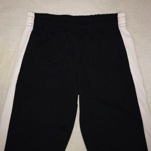 svarta byxor med vit rand på vardera sida. använda en gång.