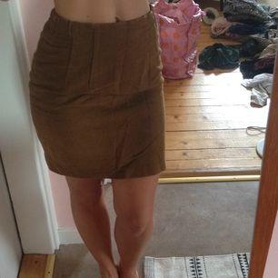 Vintage kortare pennkjol i ljusare brun. Fin till hösten! Dragkedja baktill med litet sprund under rumpan.