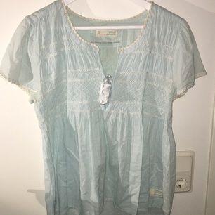 En twenty-four-seven blouse från Odd Molly.  En ljusblå blus med snörning mellan brösten är  i storlek 3, använd en gång!
