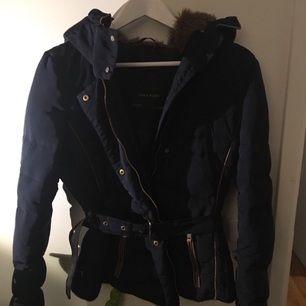 En mörk blå vinterjacka med bälte i midjan från Zara, storlek XL, liten i storleken. Använd men är i fint skick !