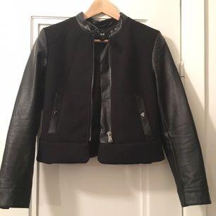Jättefin bikerjacka i ull- och läder imitation. Knäppning med dragkedja och knappar vid halsen.