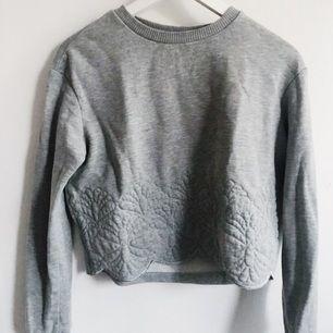 Croppad sweatshirt med muddar på ärmarna. Ljusgrå med sytt mönster ner till! Nyskick då jag nästan aldrig använt den för att jag inte trodde att den var croppad när jag köpte den! Frakt tillkommer