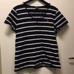 Ralph Lauren T-Shirt. Blåvit randig där färgen är mörkblå. Material i bomull och fräsch i tyget.
