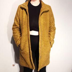 Gul/grön melerad kappa i ullblandning i storlek 38 från Monki säljes för 200kr, frakt tillkommer. Kappan är använd 2 gånger och är därav i väldigt fint skick. Betalning sker via swish.   Pris: 200kr  Storlek: 38