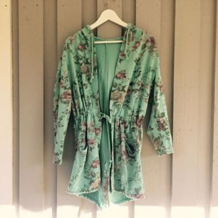 Underbar turkos kaftan/tröja mönstrad med blommor och blad! Har luva och går att dra åt i midjan! (90kr med frakt)