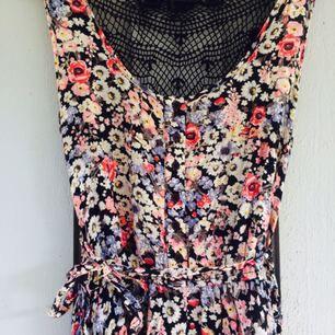 Underbar, blommig klänning med band i midjan och broderad rygg.  Frakt 30kr.