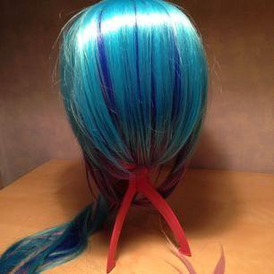 Ljus/mörk blå, rosa, lila peruk med längre del bak. Perukställning/hållare inkluderat om önskat.