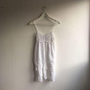Vit klänning som är virkad upptill. Kan användas som strandklänning. Aldrig använd