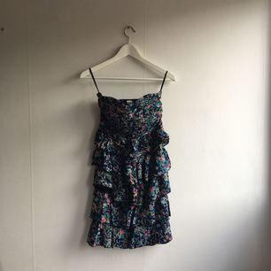 Mönstrad klänning med volang nertill. Aldrig använd.