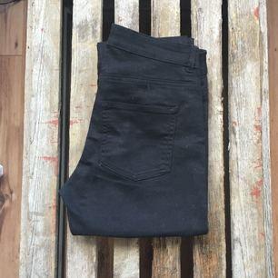 Stretchiga svarta byxor från HM med gulddetaljer. Aldrig använda.