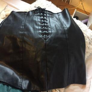 Kjol från bikbok i läder imitation med snörknytning fram och dragkedja bak. Fint skick
