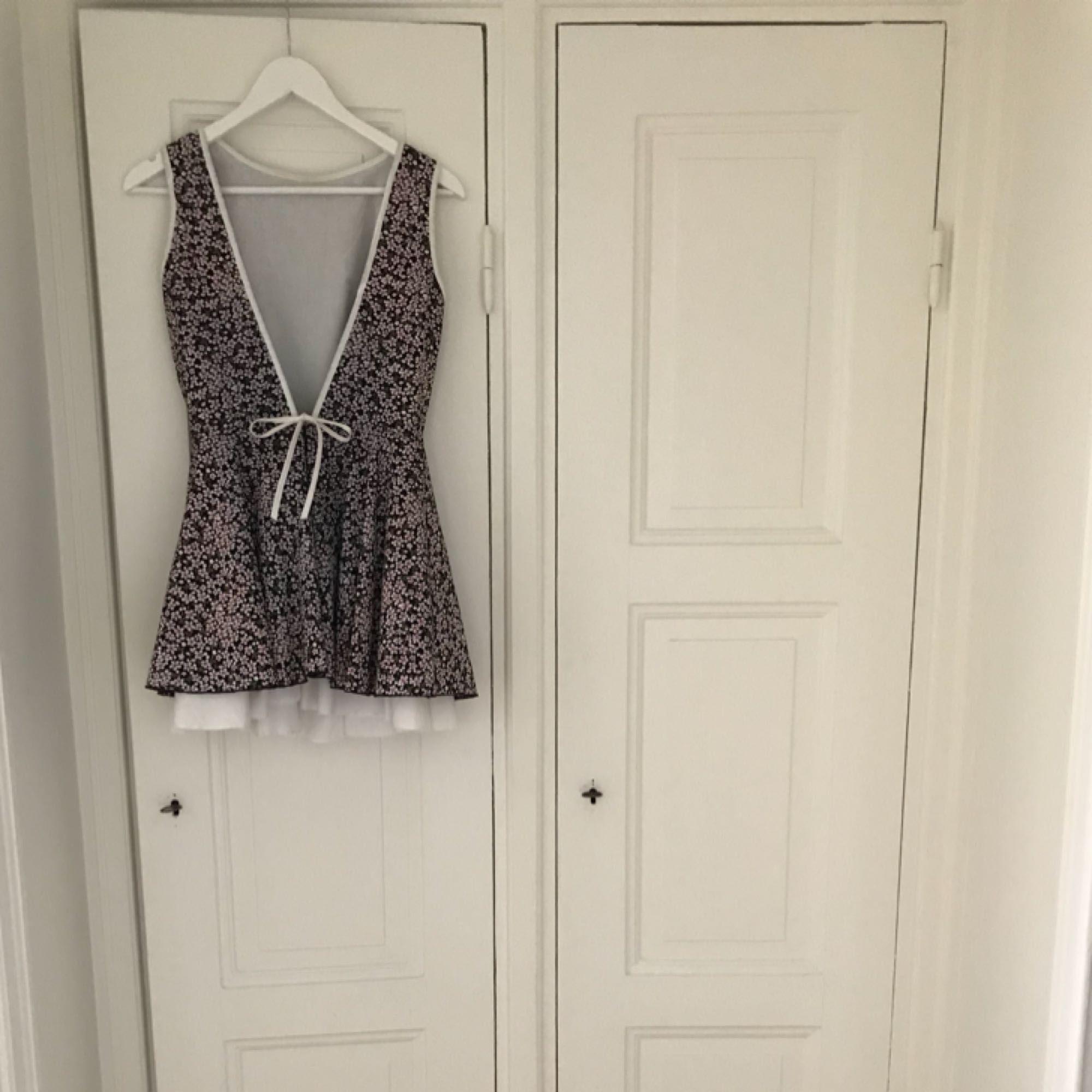 Superfin sommarklänning i vitt/lila. Underkjol i tyll för vippig kjol. Öppen, djup v-ringad rygg. Använd ett fåtal gånger.. Klänningar.
