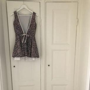 Superfin sommarklänning i vitt/lila. Underkjol i tyll för vippig kjol. Öppen, djup v-ringad rygg. Använd ett fåtal gånger.