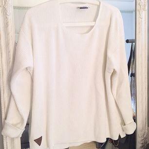 Stickad vit tröja med liten läderpatch nedtill.
