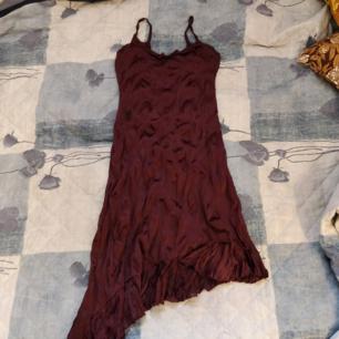 Mörklila klänning i strl 36, använd men i fint skick! Snörning på ryggen och tyget är i 100% polyester. Obs att en söm har gått sönder längst ner på volangen men syns inte så tydligt.