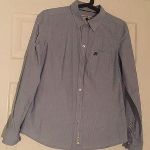 """Skjorta med vita o blåa ränder, men ränderna är så pass små att den ser bara blå ut. Från kappahls """"Hampton Republic"""", det är det märket som finns på bröstfickan. Endast använd en gång. Riktigt snygg på!"""