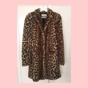 Lång leopardmönstrad kappa i fuskpäls. Två fickor fram.  Något sliten och nopprig i pälsen, så som fuskpäls blir efter ett tag, samt ett brännmärke, men som inte syns pga mönstret. Därav det billiga priset :)