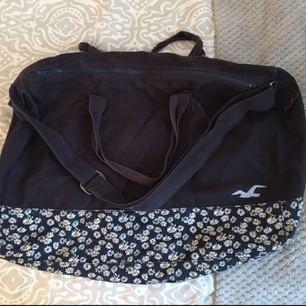 Hollister väska, som fungerar både som skolväska eller weekendbag mm. I väldigt bra skick, kan skicka fler bilder vid intresse! Mörkblå med blommigt mönster nertill och ett stort innerfack.