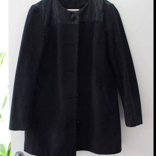 Mörkgrå kappa med fuskläder detalj. Liten i storleken så den passar en storlek M!  Köparen står för eventuell frakt.