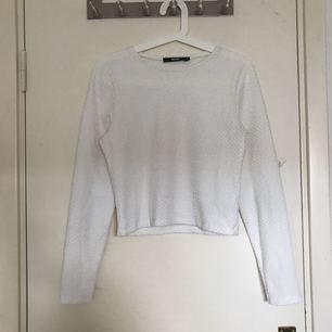 Croppad tröja i något slags ribbat mönster. Den passar bra till ett par jeans eller en söt kjol. Jag är en XS-S så jag har använt den som lite översize vilket har fungerat bra. Tröjan är använd 3-4 ggr endast.    Frakt ingår INTE i priset.