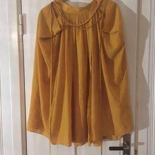 Fin vid kjol i senapsgul, från H&M. Två fickor, och ett tunt band att knyta i midjan. 100% polyester.  Fint skick. Har swish, köparen står för frakt.