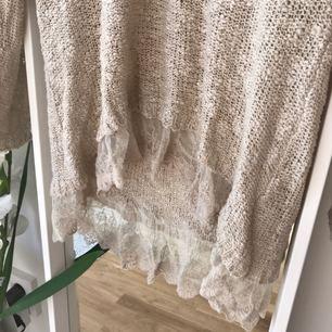 Fin stickad tröja med volang i spets nertill. Använd ett fåtal gånger.  Kan skickas mot frakt kostnad