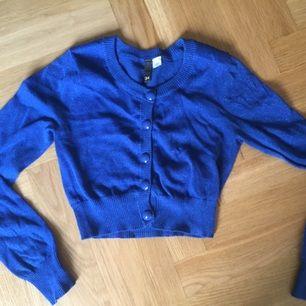 Blåglittrig kort tröja med fina knappar. Köpt för några år sedan, men endast använd ett fåtal ggr.
