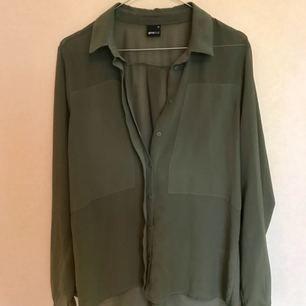 Militärgrön, tunn blus från Gina. Bra till fest och vardags, hänger snyggt på kroppen.   Frakt ingår!