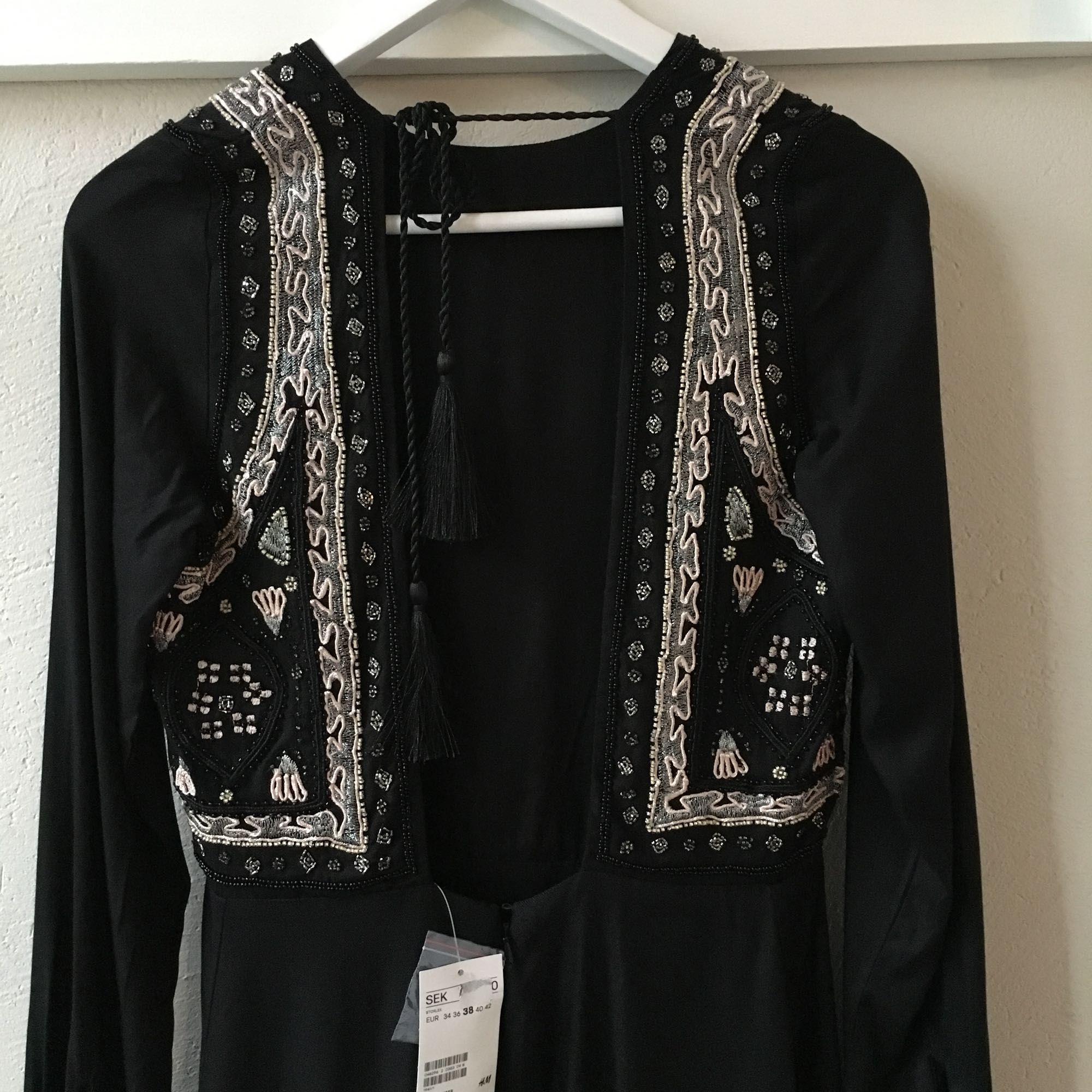 6ee2a3dcd502 Djup urringning i Vacker och lyxig klänning med stenar från H&M som aldrig  är använd.