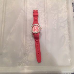 Röd klocka i silikon med strass runt urtavlan. Aldrig använd!