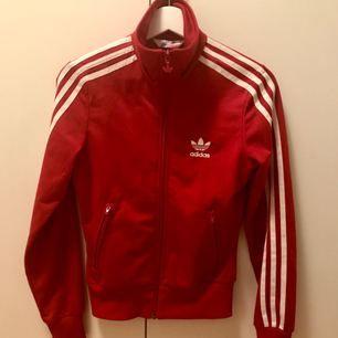 Röd Adidas tröja/track jacket/jacka, står storlek 32 i den men den är mer som en 34 enligt mig. Det är två jättesmå hål ovanför loggan fram, annars i perfekt skick🍎