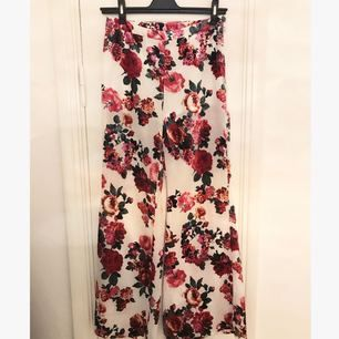 Fantastiska byxor i vit chiffong med blommor i sammet från H&M Divided. Det vita tyget är aningen transparent och byxorna har insydda shorts. Bara använda en gång innan de blev för små för mig, som nya!