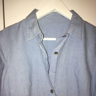 Blå skjorta som tyvärr saknar två knappar. Men om du som mig föredrar att ha en tröja över eller ha skjortan uppknäppt funkar den! Mjukt material och figursydd. Skriv till mig för fler bilder, mått eller andra frågor! :)