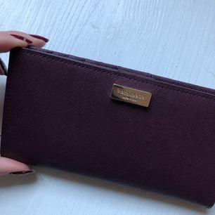 Äkta Kate Spade plånbok.  Flera kort hållare samt dragkedja på ett fack.  Använd 2-3 gånger, som ny med inga repor eller fläckar.   Finns i centrala Stockholm eller köpare betalar frakt.
