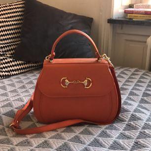 Orange väska. Påminner om Gucci och Hermès. Köpt second hand. Axelrem är avtagbar. Mycket fint skick!