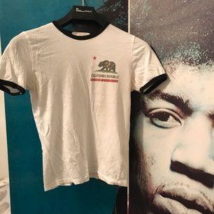 Vit tshirt från Urban outfitters. Enda defekten är svaga deofläckar (syns på bild). Dessa syns inte när tröjan är på. Fraktkostnad tillkommer