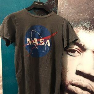 Helt oanvänd tshirt med NASA-tryck. Trycket ser lite urtvättat ut så man är medveten om det. (Syns på bild två) Fraktkostnad tillkommer