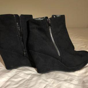 Ett par svarta högklackade skor med en fake dragkedja på sidan som detalj. Är i nyskick