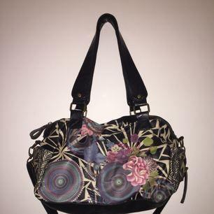Snygg handväska från märket Desigual. Den har två korta handtag och ett längre justerbart. Den är använd men i bra skick. Det finns små fack med dragkedjor på insidan.