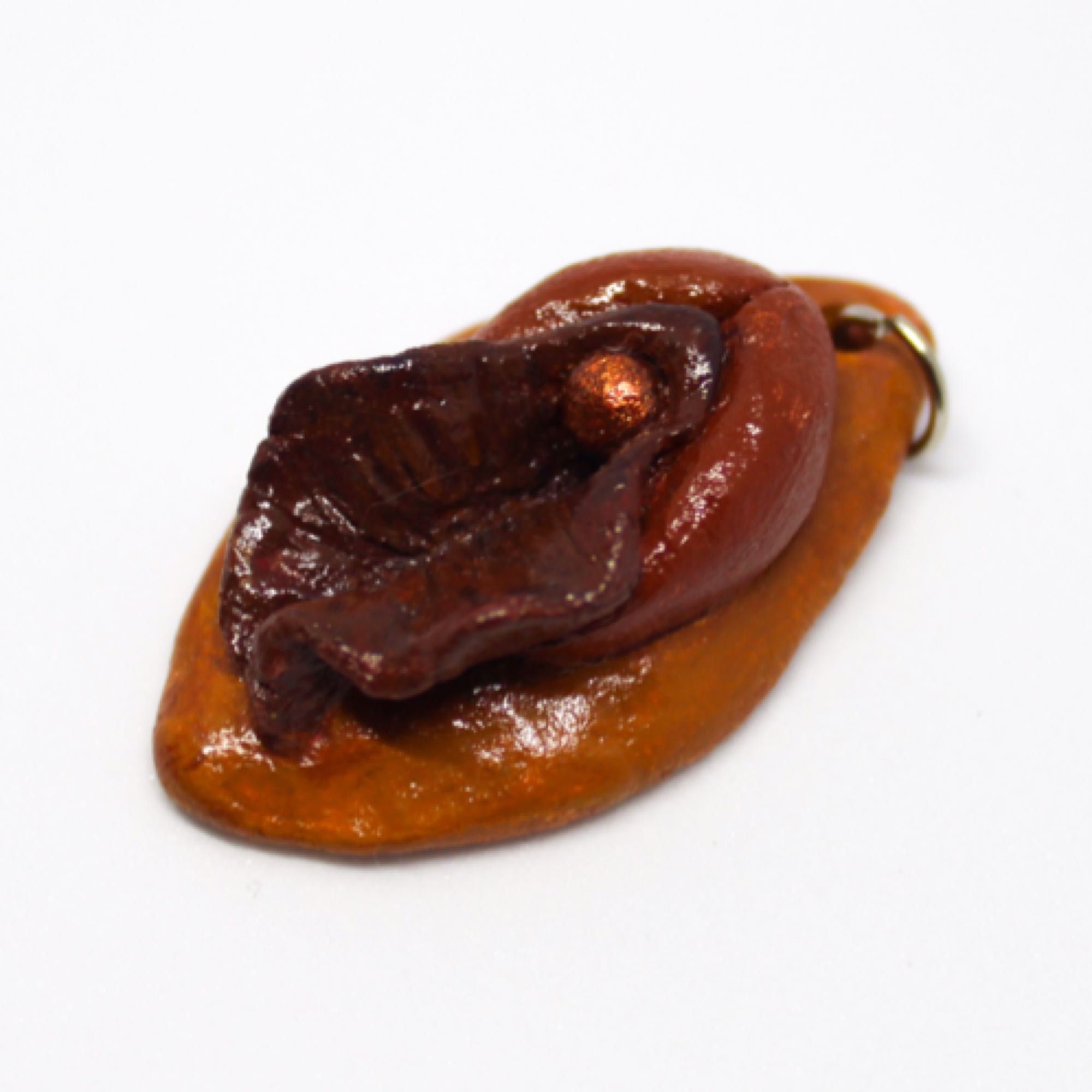 Liten vulva i lera. Mått 36mm x 21mm. Kedja eller