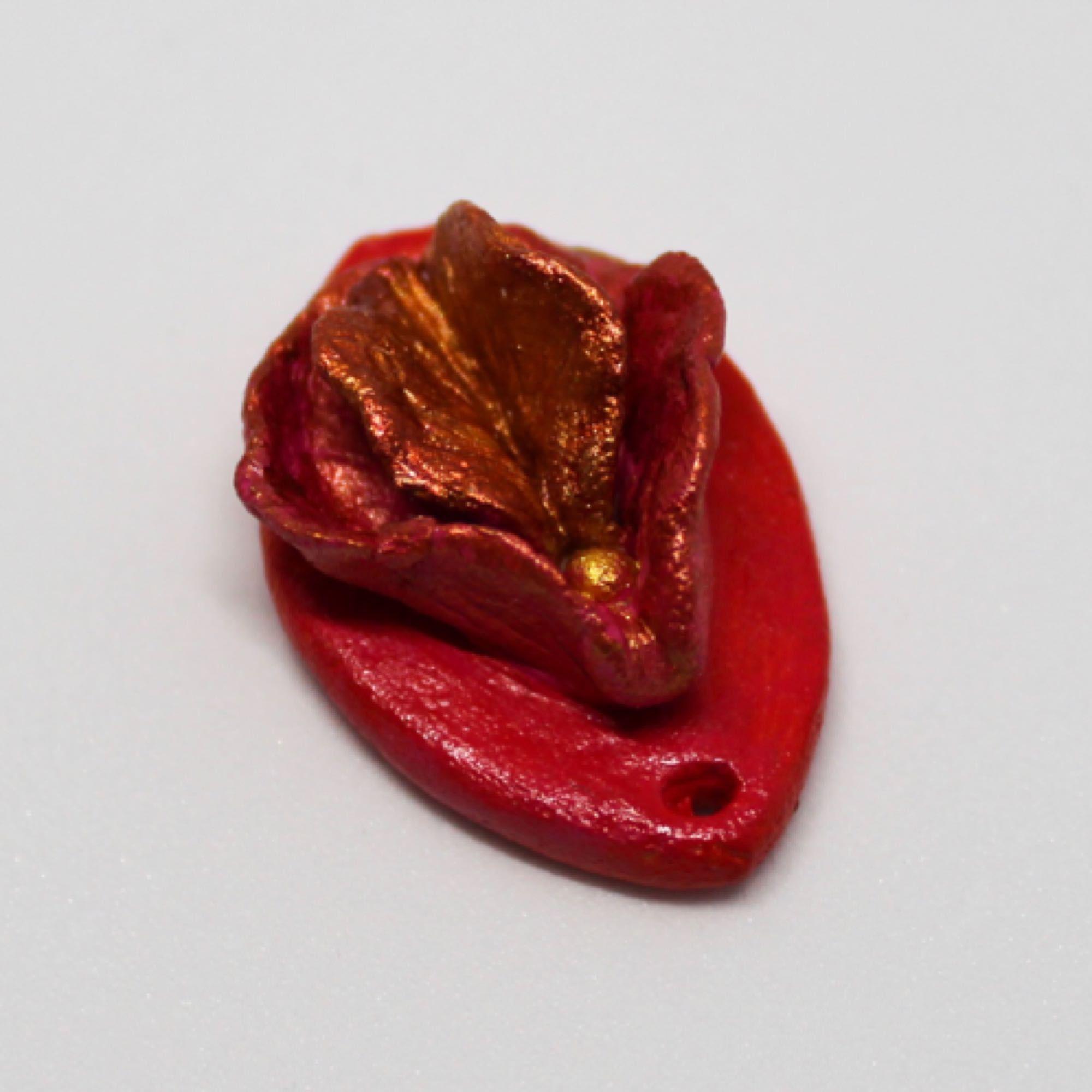 Liten vulva i lera. Mått 28mm x 18mm. Kedja eller