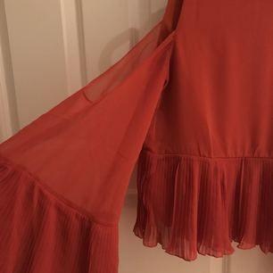 Blus med vida räfflade ärmar från Nelly. Färgen är en rödorange blandning. Skitsnygg på kroppen! Frakt på 20kr❤🌹
