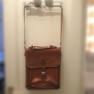 Välsydd konjaksfärgad läderväska med 2st stora fack och ett mindre. Justerbar axelrem. B 26cm H 29 cm D 10 cm