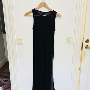 Transparent klänning från Monki med höga slits på sidorna som går till midjan ungefär. Passar perfekt som överklänning med en tight kort klänning under eller ett par höga jeans.